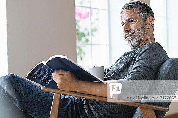 Älterer Geschäftsmann mit Kaffeetasse und Buch  der wegschaut  während er zu Hause sitzt Älterer Geschäftsmann mit Kaffeetasse und Buch, der wegschaut, während er zu Hause sitzt
