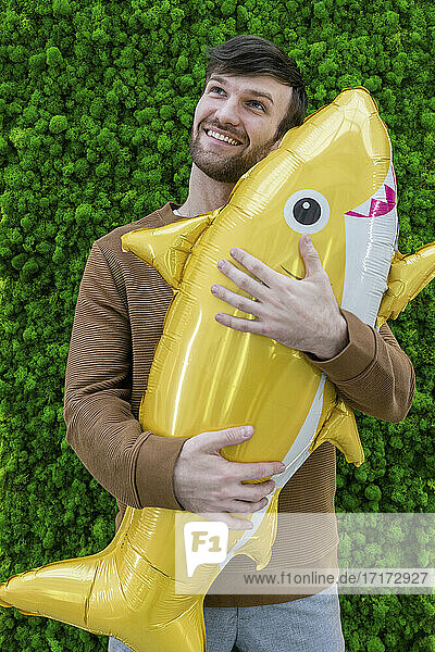Smiling male entrepreneur day dreaming while holding inflatable shark against green backdrop