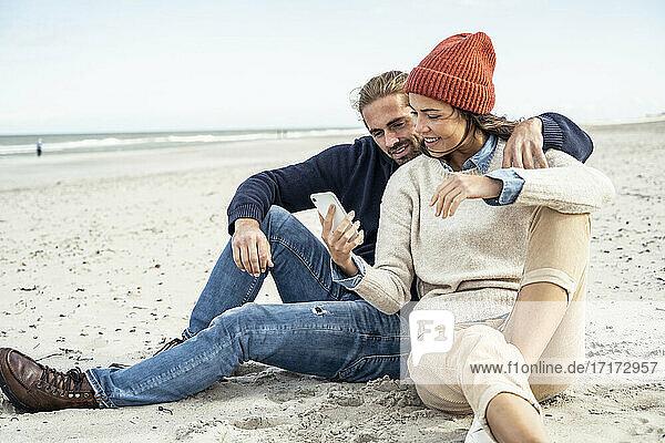 Junges Paar sitzt zusammen am Strand und benutzt ein Smartphone Junges Paar sitzt zusammen am Strand und benutzt ein Smartphone