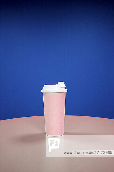 Reusable coffee cup on table against blue background