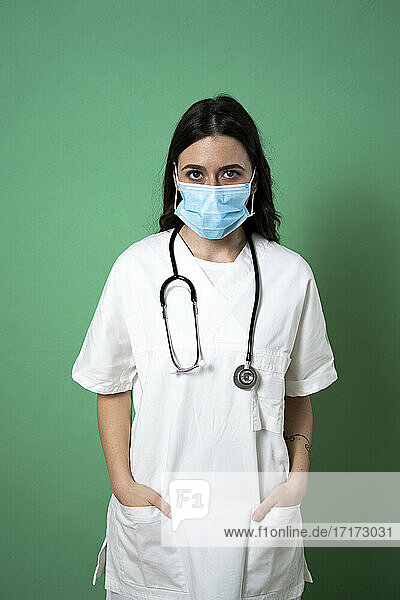 Female doctor with hands in pockets against green background during pandemic