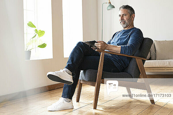 Mature businessman with digital tablet looking away while sitting on armchair at home