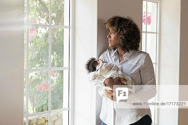 Nachdenkliche Frau mit Baby,  die wegschaut,  während sie zu Hause am Fenster steht