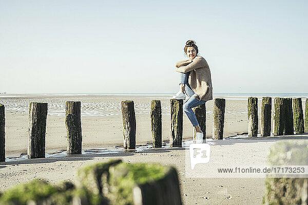 Junge Frau  die am Wochenende auf einem Holzpfosten am Strand sitzt und träumt Junge Frau, die am Wochenende auf einem Holzpfosten am Strand sitzt und träumt