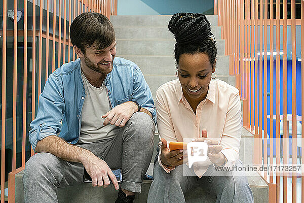 Smiling business people using mobile phone and talking while sitting on staircase at work place