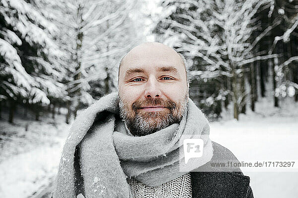 Smiling mature man wearing scarf against bare trees in sow