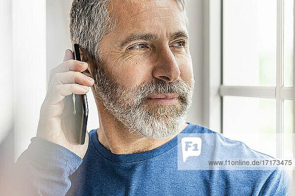 Älterer Geschäftsmann  der im Stehen zu Hause mit seinem Handy telefoniert Älterer Geschäftsmann, der im Stehen zu Hause mit seinem Handy telefoniert
