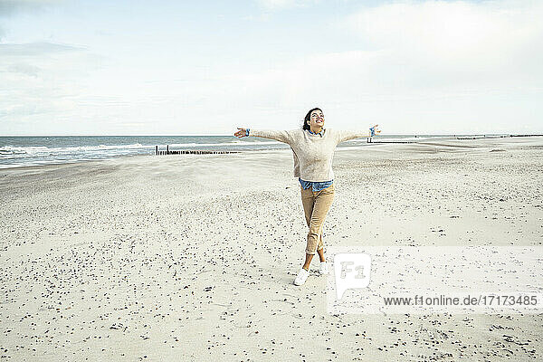 Portrait of young woman walking on sandy beach with raised arms