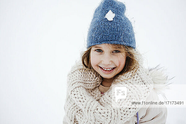 Cute smiling girl in knitted warm clothing during winter