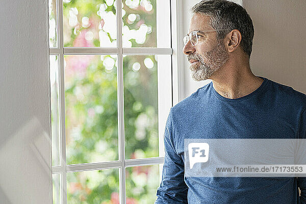 Nachdenklicher Geschäftsmann schaut durch das Fenster  während er zu Hause steht Nachdenklicher Geschäftsmann schaut durch das Fenster, während er zu Hause steht
