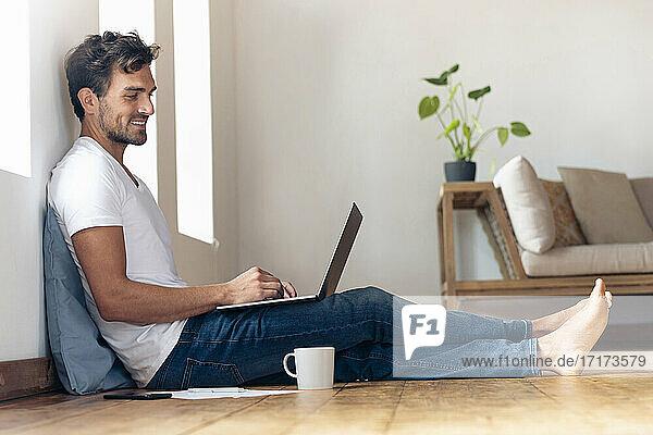 Lächelnder Mann  der einen Laptop benutzt  während er zu Hause auf dem Boden sitzt Lächelnder Mann, der einen Laptop benutzt, während er zu Hause auf dem Boden sitzt