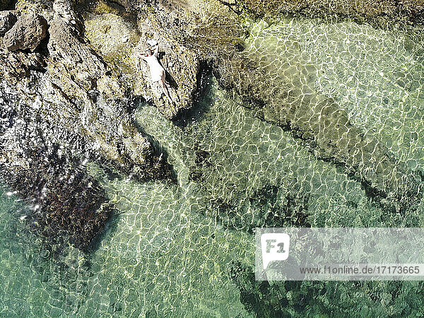 Aerial view of mature woman lying on rock at beach during sunny day
