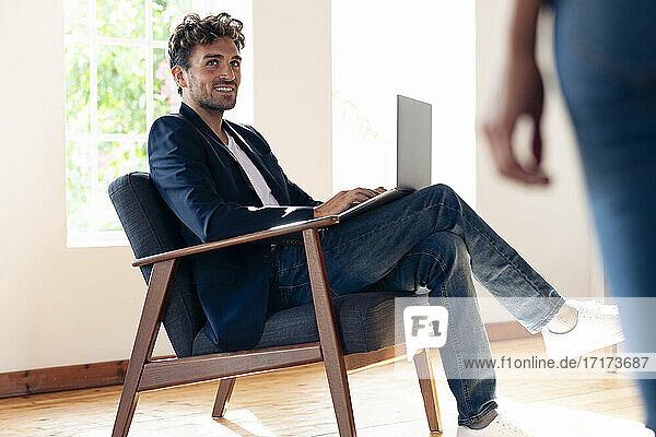 Lächelnder Geschäftsmann  der eine Frau ansieht  während er zu Hause am Laptop arbeitet Lächelnder Geschäftsmann, der eine Frau ansieht, während er zu Hause am Laptop arbeitet