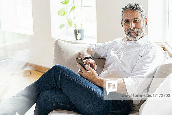 Geschäftsmann mit Mobiltelefon  der wegschaut  während er zu Hause sitzt Geschäftsmann mit Mobiltelefon, der wegschaut, während er zu Hause sitzt