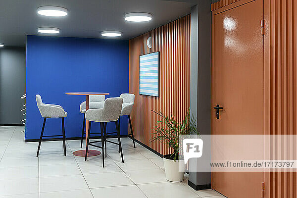 Table and chair against blue wall in office