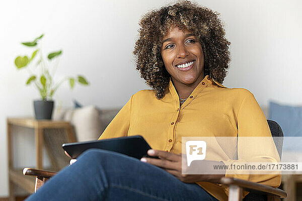 Lächelnde Frau  die ein digitales Tablet benutzt  während sie zu Hause sitzt Lächelnde Frau, die ein digitales Tablet benutzt, während sie zu Hause sitzt