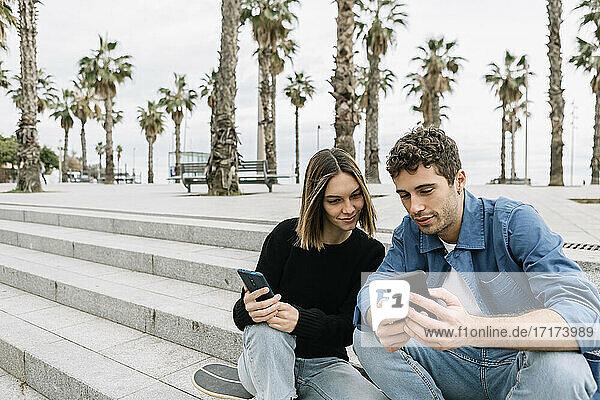 Pärchen schaut im Freien auf Smartphones