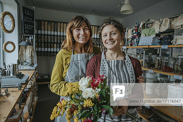Store owner with female colleague holding bunch of flowers while standing in zero waste store