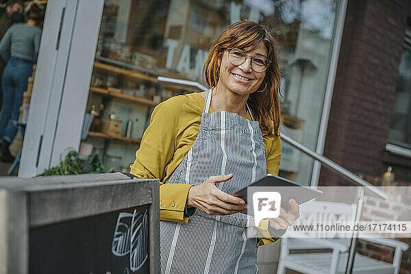 Smiling female entrepreneur holding digital tablet while standing against retail shop