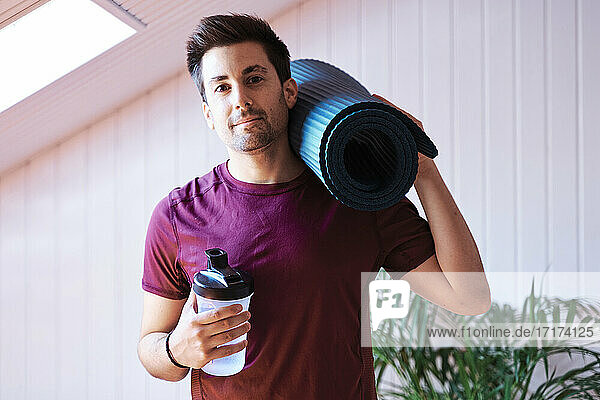 Man ready for exercise with mat and bottle