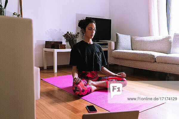 Young woman Property Released (PR)acticing yoga and meditation at home
