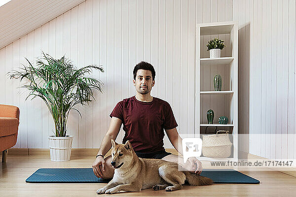 Man sitting on exercise mat with pet dog