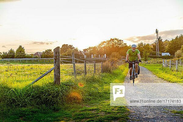 Man mountain biking on rural path