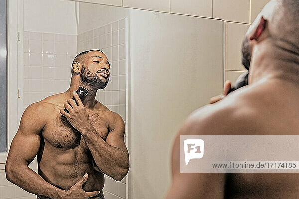 Man shaving with electric razor  looking in mirror