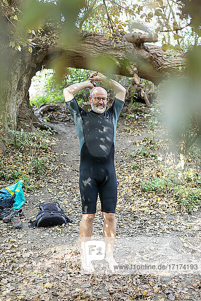 Man putting on wetsuit outside  Property Released (PR)eparing for swim