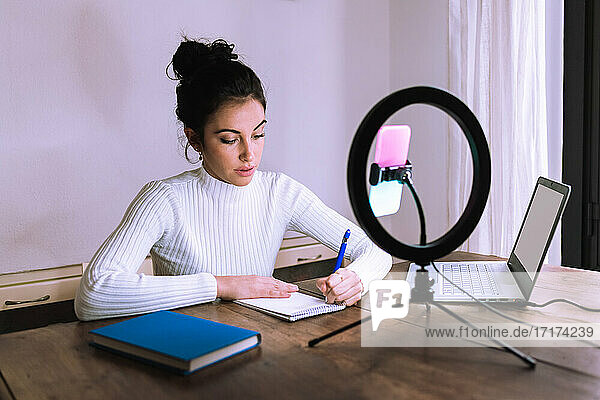 Young woman working from home with laptop  phone and ring light