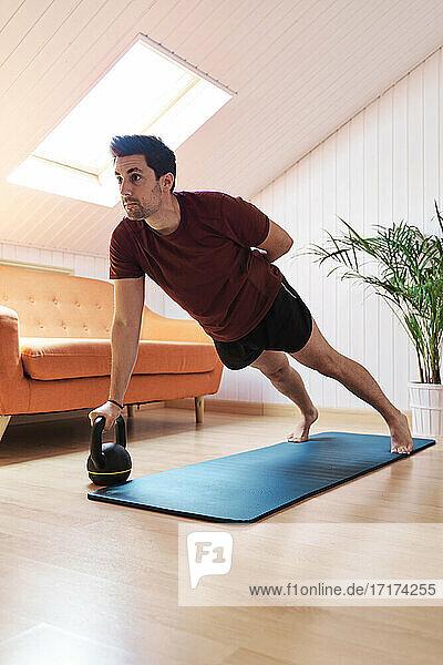 Man exercising at home  using kettlebell
