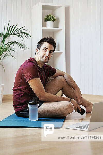 Man at home with exercise mat and laptop