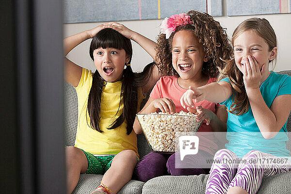 Three girls watching tv eating popcorn
