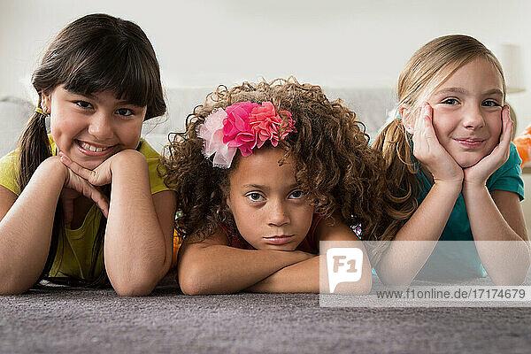 Portrait of three girls lying on front