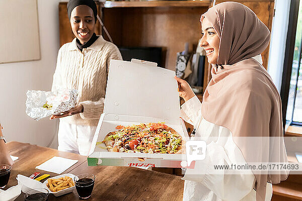 Young women setting out takeaway meal together