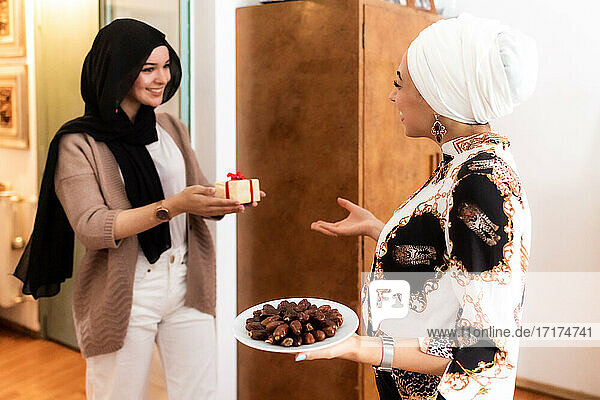 Young muslim women with gift and dates