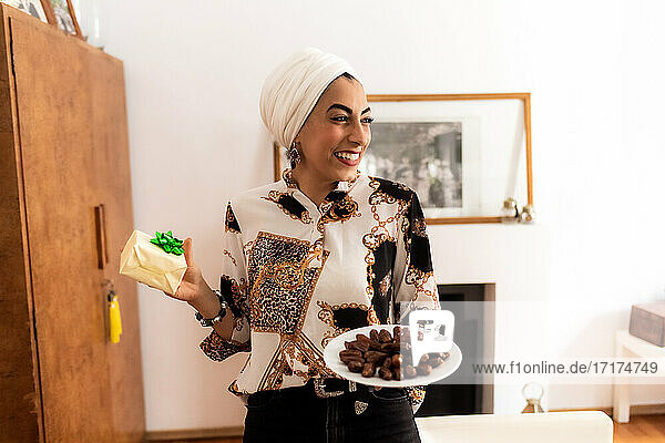 Young muslim woman with plate of dates and a gift