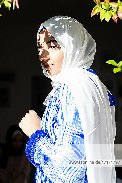 Portrait of young woman wearing hijab in sunlight and shadow