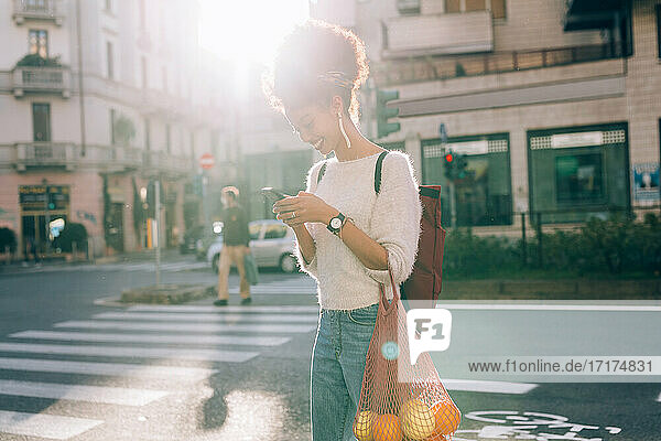 Young woman in city  looking at phone