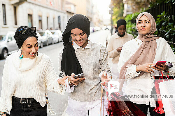 Female friends on shopping trip  looking at phone