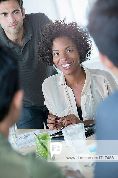Informal portrait of female office worker with colleagues