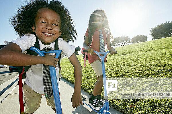 Ein 6-jähriger Junge und seine ältere Schwester auf Motorrollern auf einem Weg