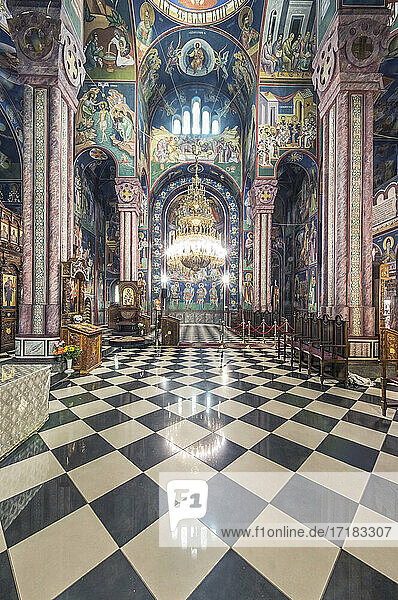 Serbian Orthodox church interior in Ljublijana  murals  painted pillars and walls  and chandelier.