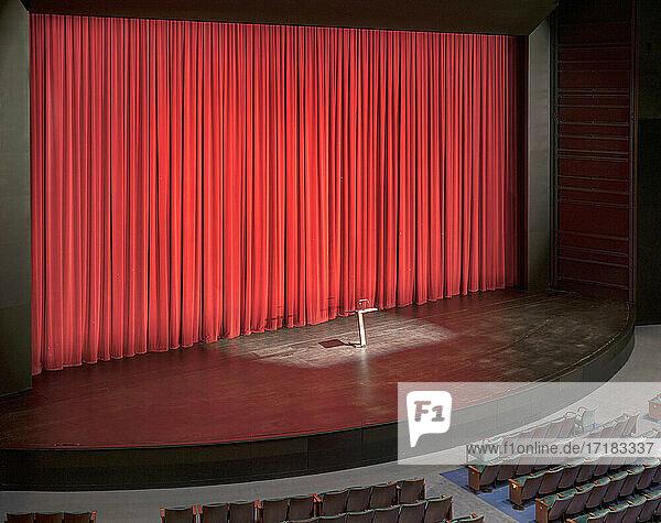 Bühne mit roten Vorhängen in einem leeren Zuschauerraum.