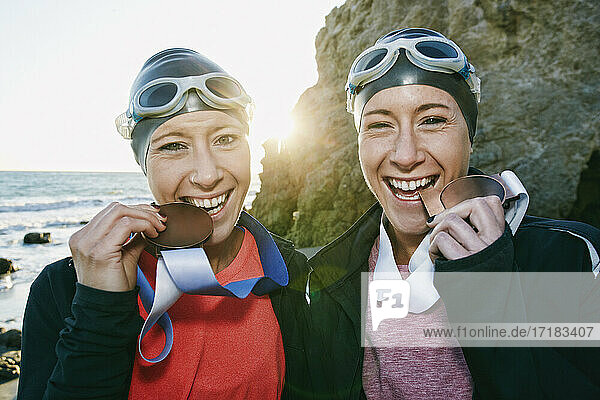 Two sisters  triathletes in swimhats and goggles wearing their large medals  winners.