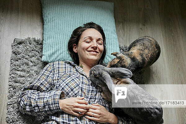 Woman lying on floor surrounded by two pet house rabbits shot from above