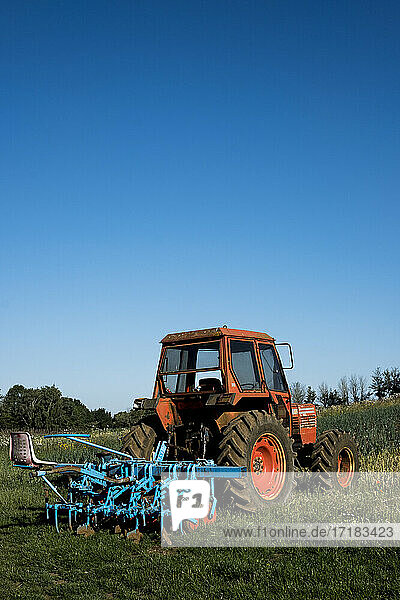 Red tractor with blue harrow on a farm.