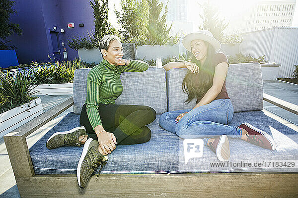 Two young women on a sofa in a rooftop garden at dusk