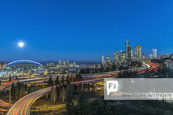 The city skyline of Seattle at night  road and bridge  downtown buildings lit up in moonlight.