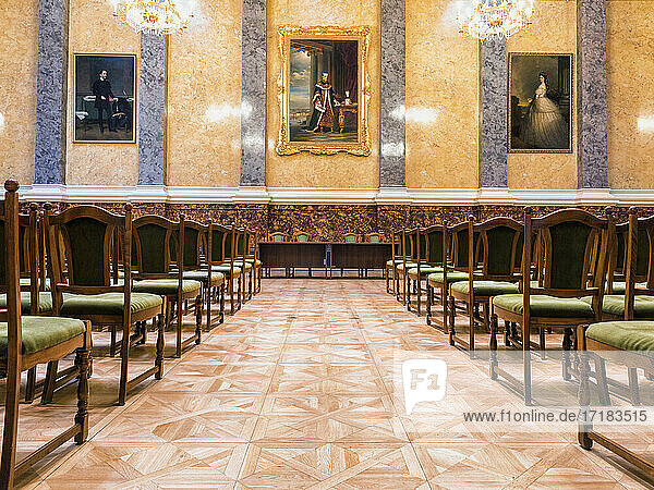 A large room with rows of chairs and chandeliers,  part of the Museum of Fine Arts in Budapest